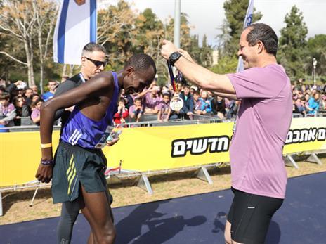 שדראק מקבל את המדליה מברקת (באדיבות מרתון ירושלים)